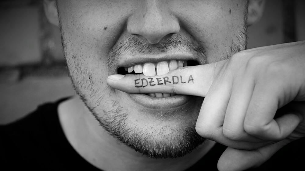 """Mann mit Finger im Mund auf dem """"ezerdla"""" steht"""