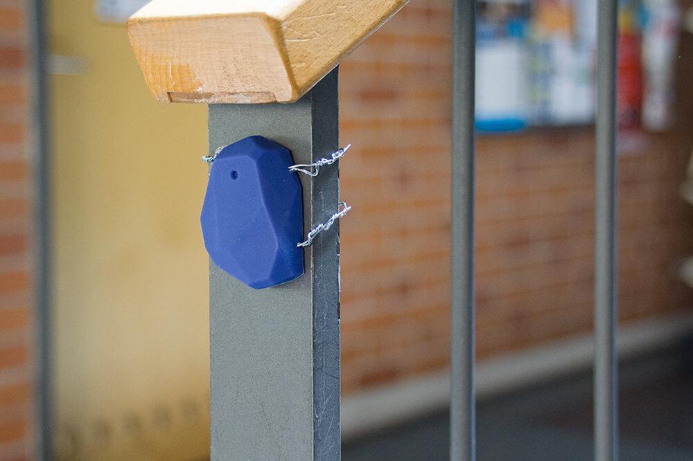 Ein blaues, etwa 5 cm großes Beacon aus Kunststoff, das mit einem Draht an einem Treppengeländer befestigt ist.