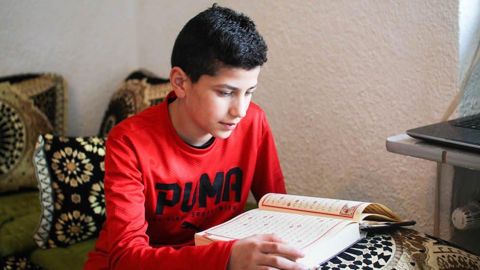 Das Kind der Familie liest im Koran.