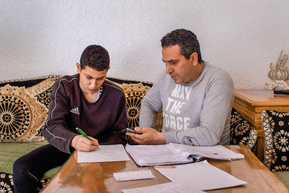 Vater Nusret und Sohn Enes sitzen gemeinsam am Tisch voll mit Schulunterlagen