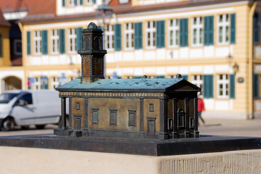 Ein Tastmodell der St. Ludwig-Kirche in Ansbach aus Metall. Im Hintergrund ist ein Gebäude und ein Lieferwagen zu sehen.
