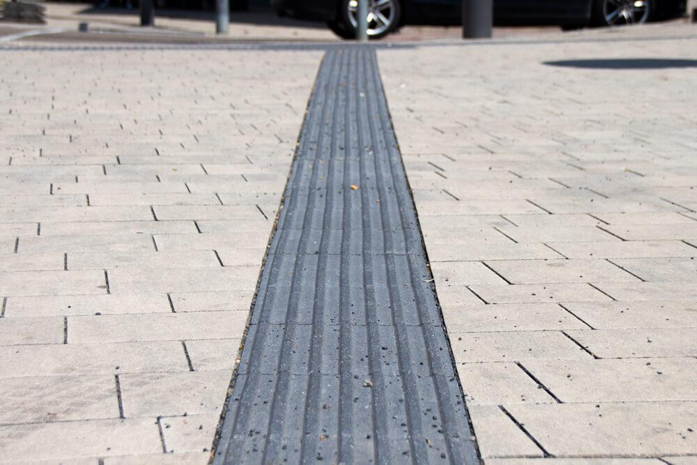 Ein Blindenleitstreifen, der von der Bildmitte in die Entfernung verläuft. Am Ende ist eine Straße und Räder eines Autos zu erkennen.