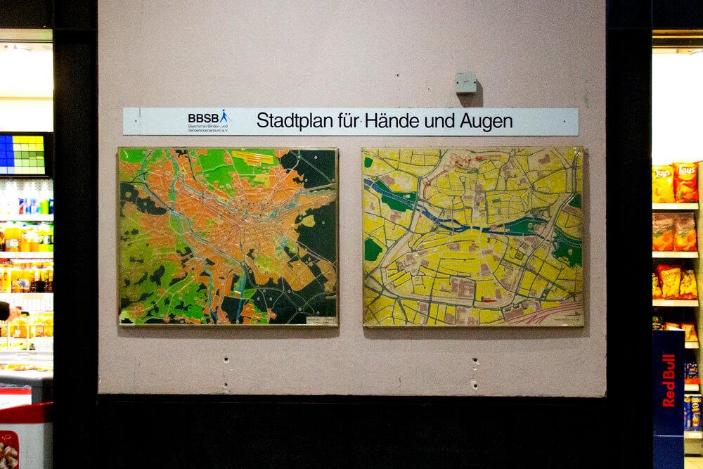 """Unter der Überschrift """"Stadtplan für Hände und Augen"""" und dem Logo des Bayerischen Blinden- und Sehbehindertenbundes sind zwei Stadtpläne von Nürnberg zu sehen. Die linke zeigt die gesamte Stadt, die rechte die Innenstadt. Im Hintergrund ist ein Ladengeschäft zu erkennen."""