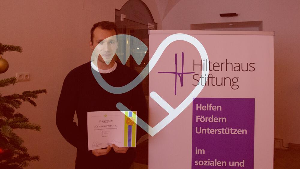 Moritz Hilpert hält eine Urkunde. Daneben ein Aufsteller der Hilterhaus-Stiftung.