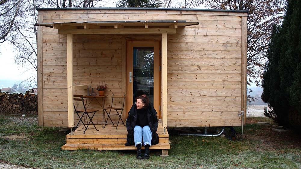 Lena sitzt vor einem Tiny House