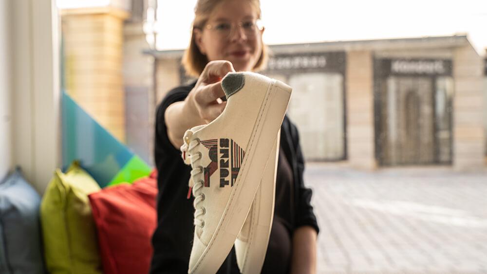 Die Gründerin Katja Wagner zeigt die ersten myturns Sneaker.